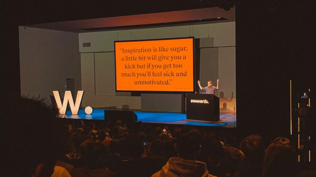 """Claudio Guglieri op het podium met een screen uit zijn talk met de volgende tekst: """"Inspiration is a bit like sugar, a little bit will give you a kick but if you'll get too much you get sick and unmotivated."""""""
