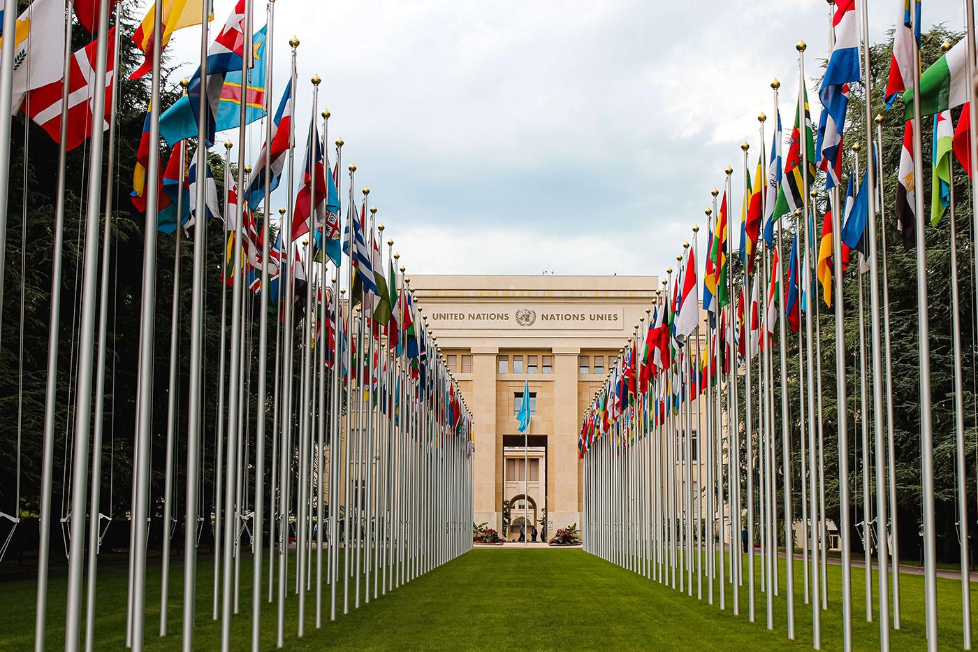Het gebouw van de Verenigde Naties in Genève, Zwitserland met de vlaggen van alle bijbehorende landen ervoor.