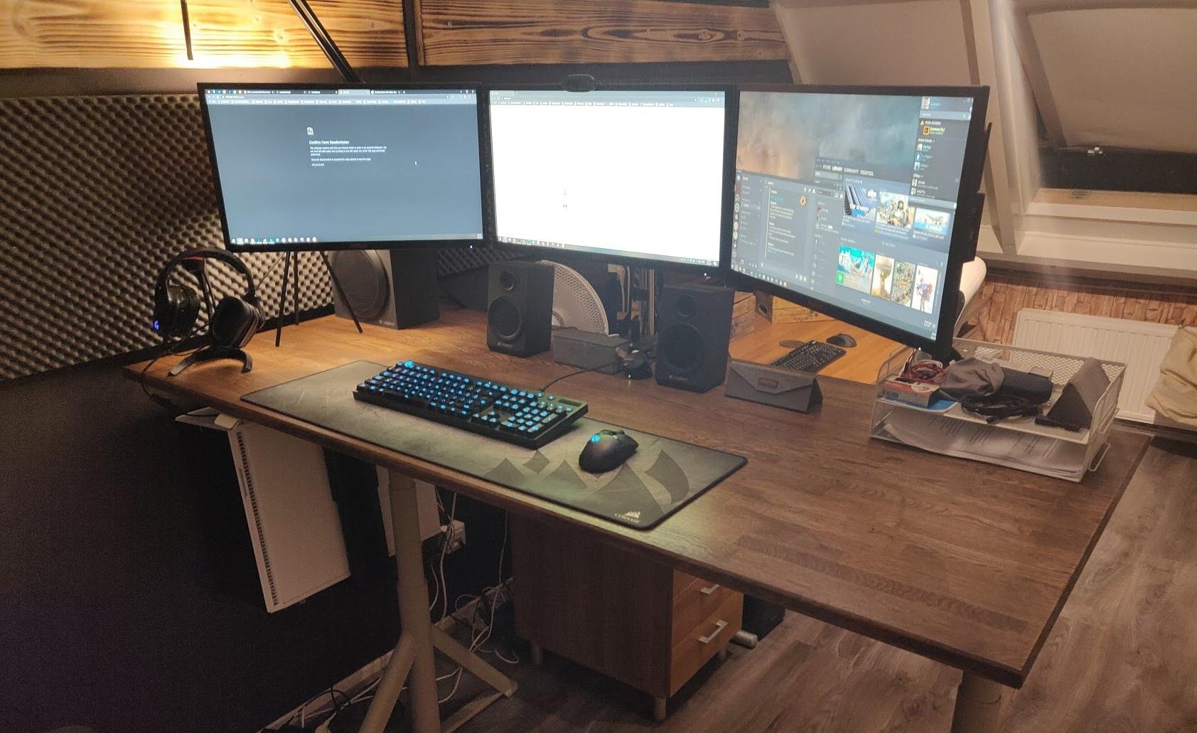 Een zit-sta bureau met drie schermen en een verlicht toetsenbord. Zijn computerkast hangt links onder het bureau.
