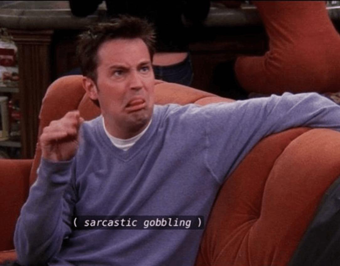 Chandler in Friends die een lelijk gezicht trekt en met zijn handen nadoet hoe iemand praat. De ondertiteling zegt
